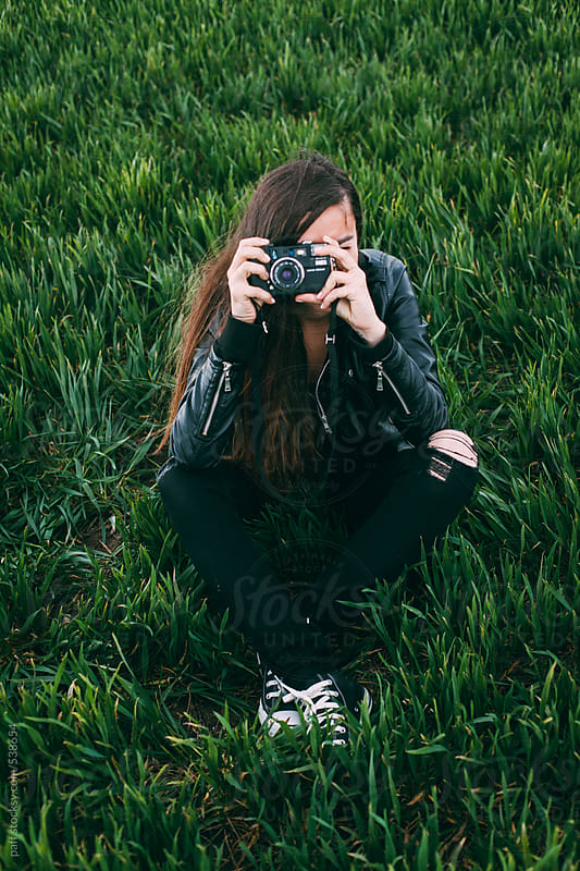 Young woman taking pictures with camera on green grass  by paff for Stocksy United