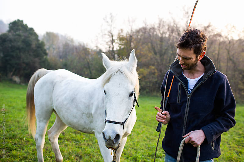 Young man talking with his horse by michela ravasio for Stocksy United