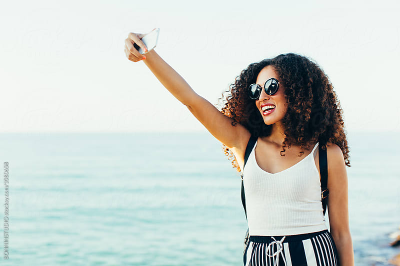 Female tourist taking a selfie near the beach.  by BONNINSTUDIO for Stocksy United