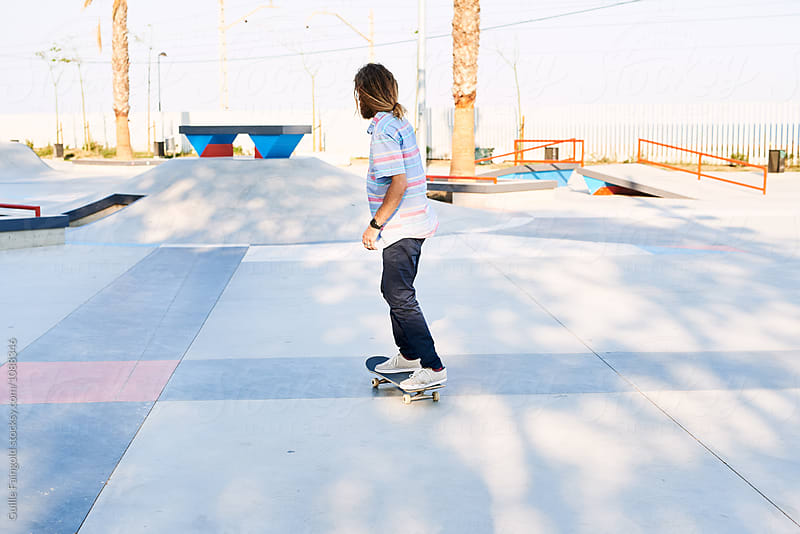 Rear view of long-haired skater riding in skate park by Guille Faingold for Stocksy United