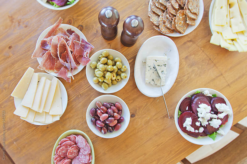 Table setting with meat, olives, cheese and breads by Carey Shaw for Stocksy United