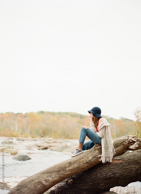 Teen girl sitting and meditating on a fallen tree at the river by Marta Locklear for Stocksy United