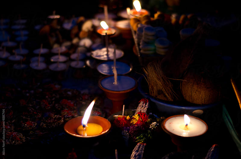 Candle's light and Buddhist religious stuff in the night darkness by Alice Nerr for Stocksy United