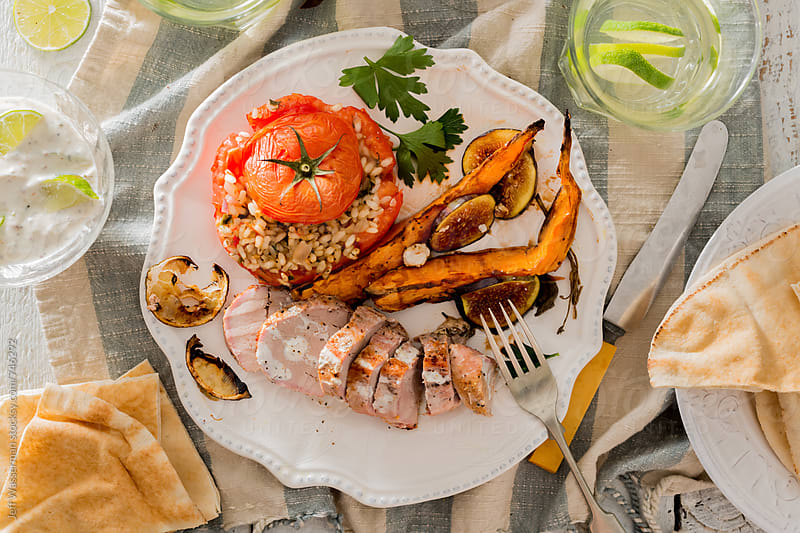 Pork Tenderloin Dinner with Sweet Potatoes and Stuffed Tomato by Jeff Wasserman for Stocksy United