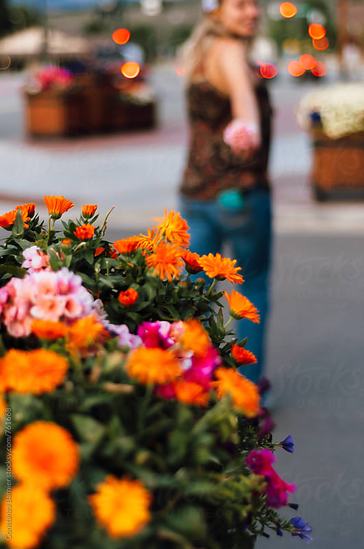 Girl picking up colorful flowers in the street by Constanza Caiceo for Stocksy United