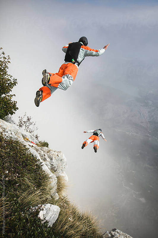 Two BASE jumpers exiting from a cliff in Italy by Wolfgang Lienbacher for Stocksy United