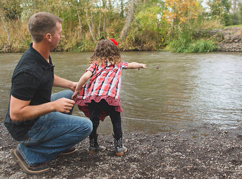 Father and daughter skip rocks in river by Tana Teel for Stocksy United