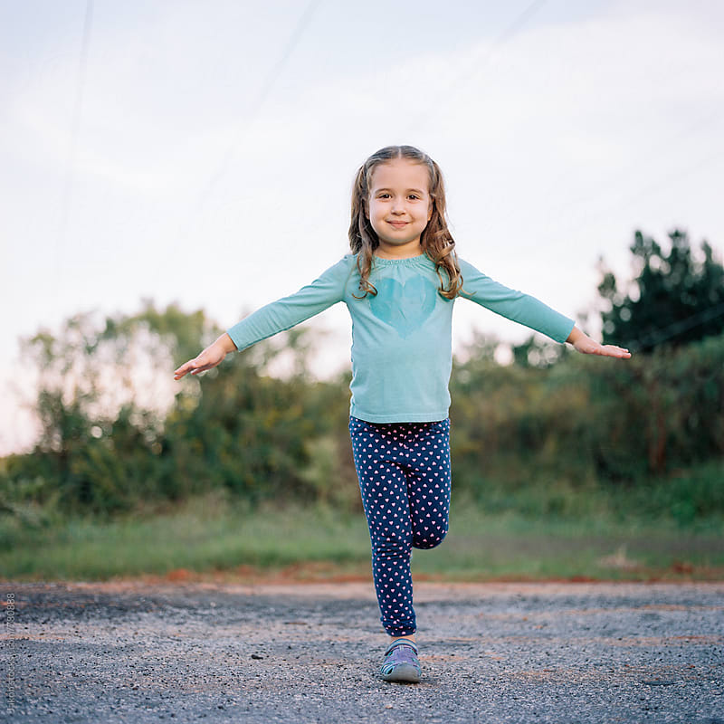 Cute young girl standing on one leg outside by Jakob for Stocksy United