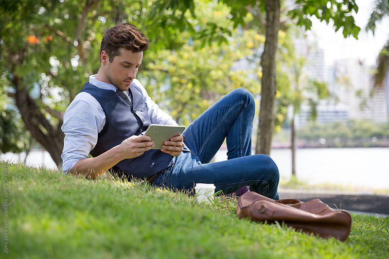 Young business man taking a break in a park - reading a book  by Jovo Jovanovic for Stocksy United