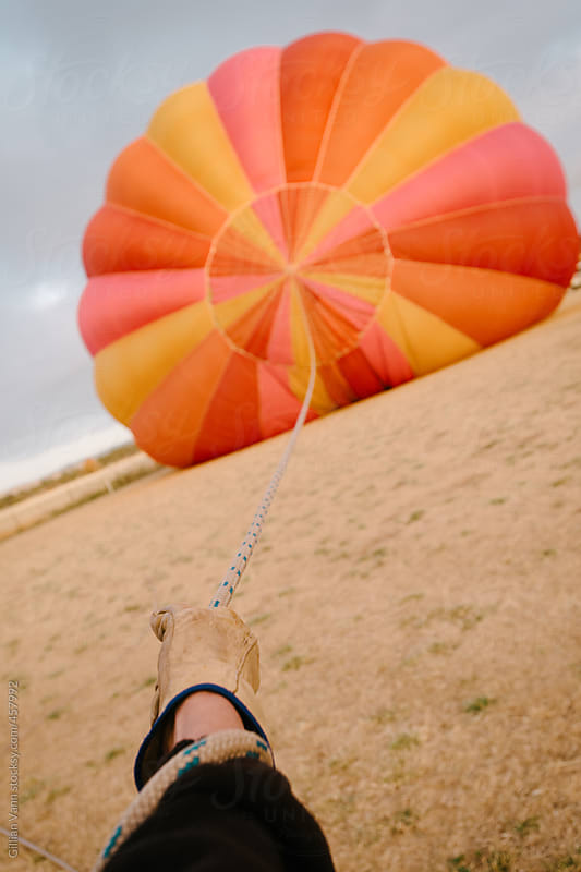 holding the guide rope as the hot air balloon inflates by Gillian Vann for Stocksy United