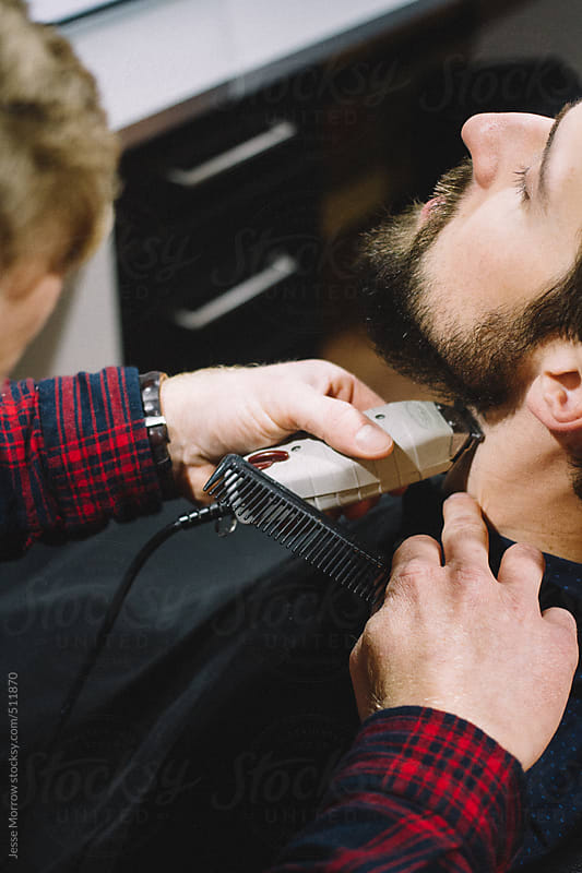 Young man gets beard trim at barber shop by Jesse Morrow for Stocksy United