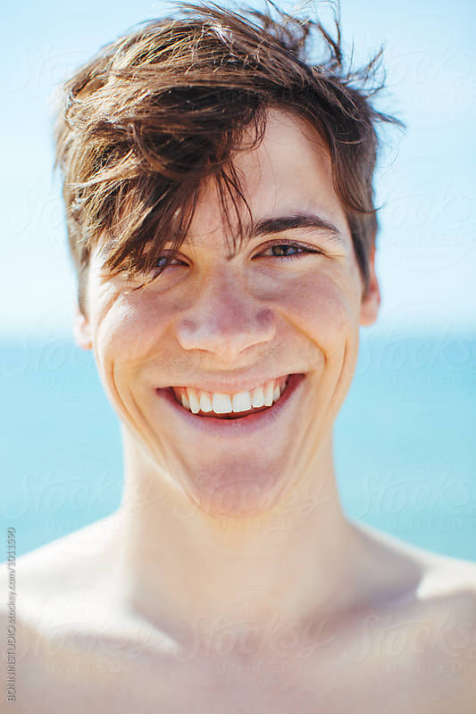 Closeup portrait of a young boy smiling on the beach. by BONNINSTUDIO for Stocksy United