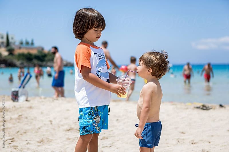 5 year old boy giving orange juice to his little brother by Nasos Zovoilis for Stocksy United