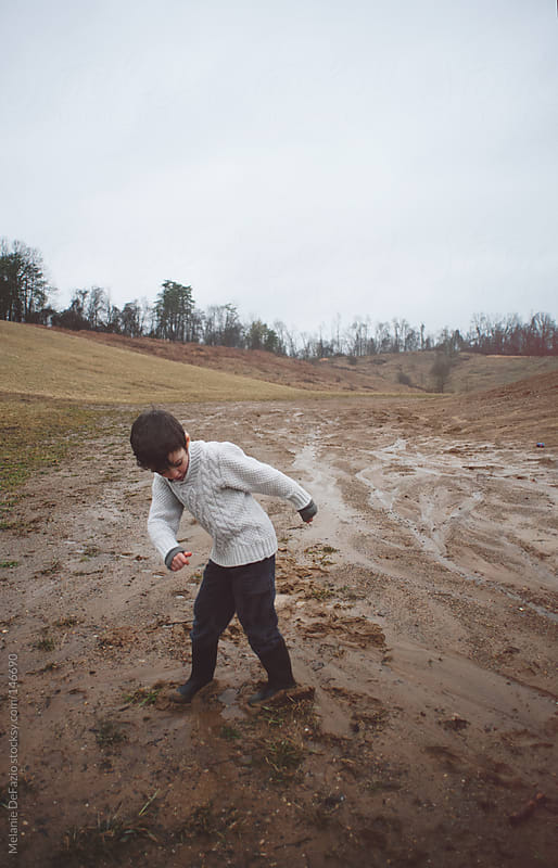 Playing in the mud by Melanie DeFazio for Stocksy United