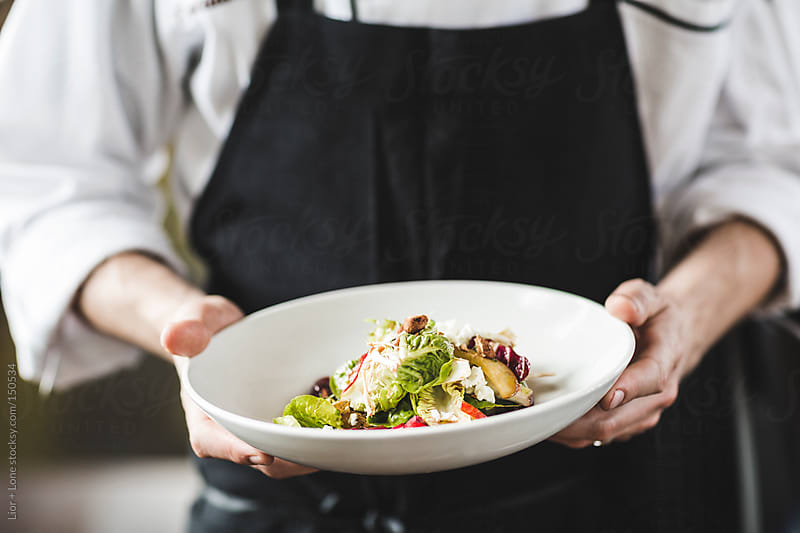 Chef holding a plate of fresh salad by Lior + Lone for Stocksy United