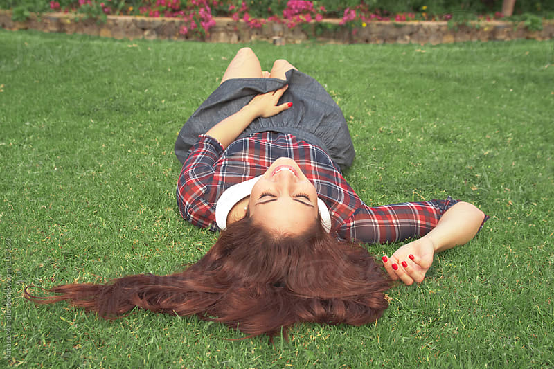 Young woman laying on the grass by Nataša Mandić for Stocksy United