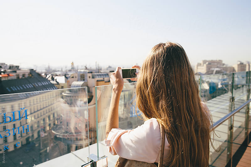 Back view of young woman taking photo of city by Andrey Pavlov for Stocksy United