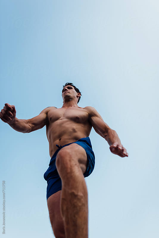 Muscular man jumping in the air by Boris Jovanovic for Stocksy United