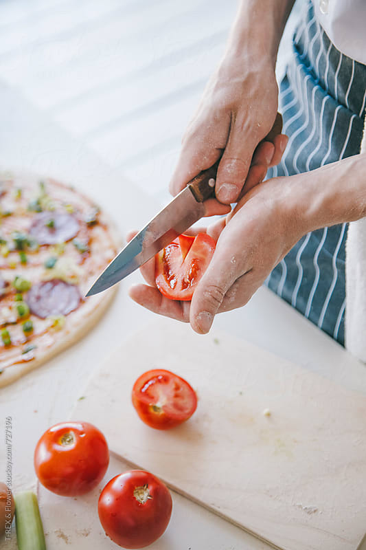 Chef cuts tomatoes for pizza by Danil Nevsky for Stocksy United