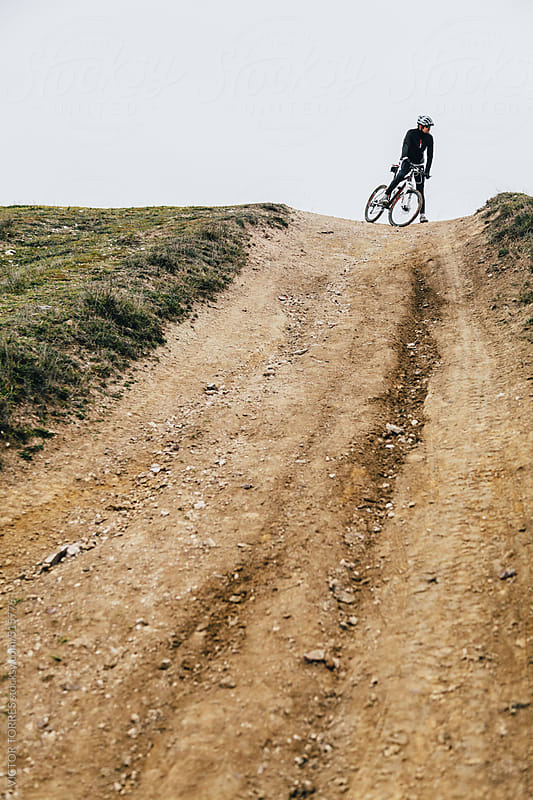 Mountain Bike Rider Prepared to Down a Hill by VICTOR TORRES for Stocksy United