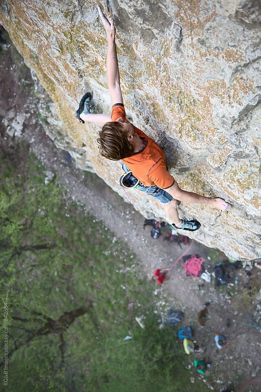 Man rock climbing on a rock face above the ground  by RG&B Images for Stocksy United