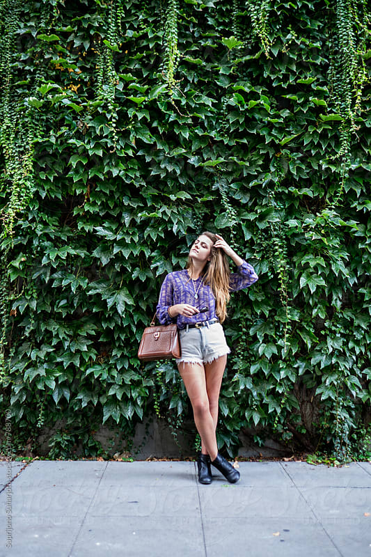 Beautiful young woman in front of a vine wall by Suprijono Suharjoto for Stocksy United