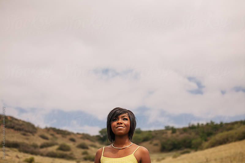 Black girl outside in yellow dress looking up by Gabrielle Lutze for Stocksy United