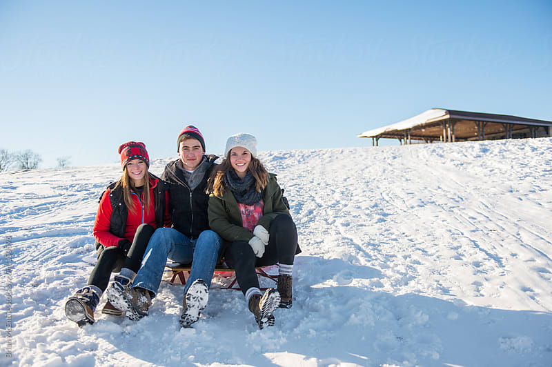 Friends sit for a photo while they are out sledding on a crisp winter day by Brian McEntire for Stocksy United