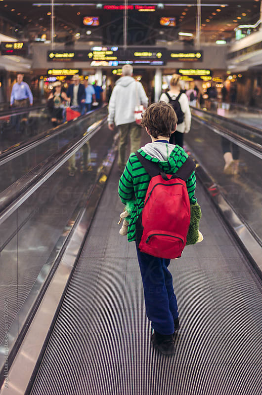 Boy on moving walkway at an airport by Angela Lumsden for Stocksy United