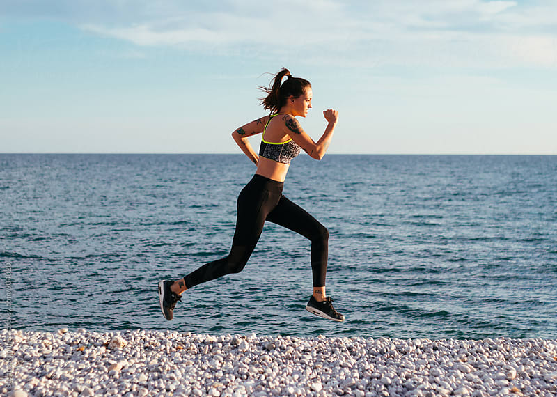 Young woman practicing running on the beach by Susana Ramírez for Stocksy United