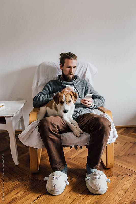 Man sitting and holding a dog by Kate & Mary for Stocksy United