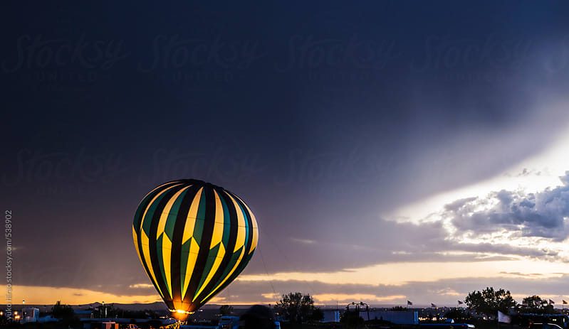 Hot air balloon glows in a stormy weather  by yuko hirao for Stocksy United
