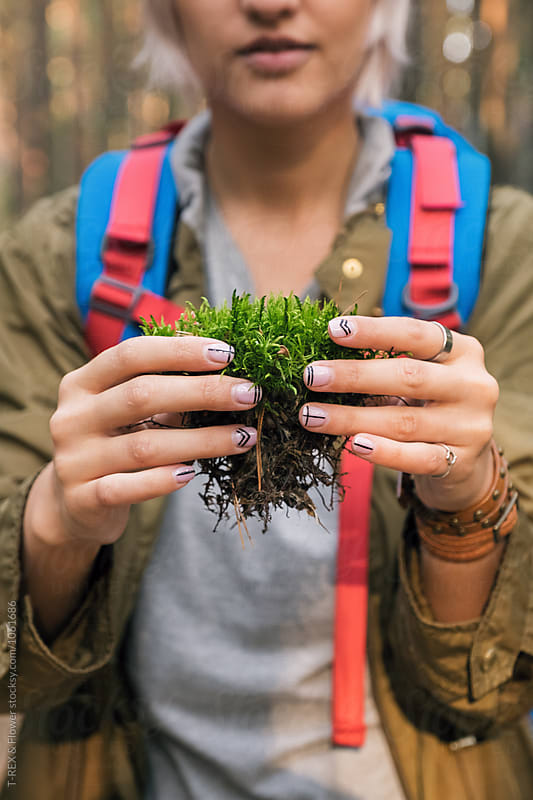 girl with beautiful manicure holding piece of soil with grass by T-REX & Flower for Stocksy United