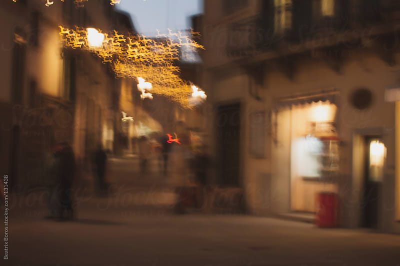 Defocused deer shape Christmas lights in the streets of Italy by Beatrix Boros for Stocksy United