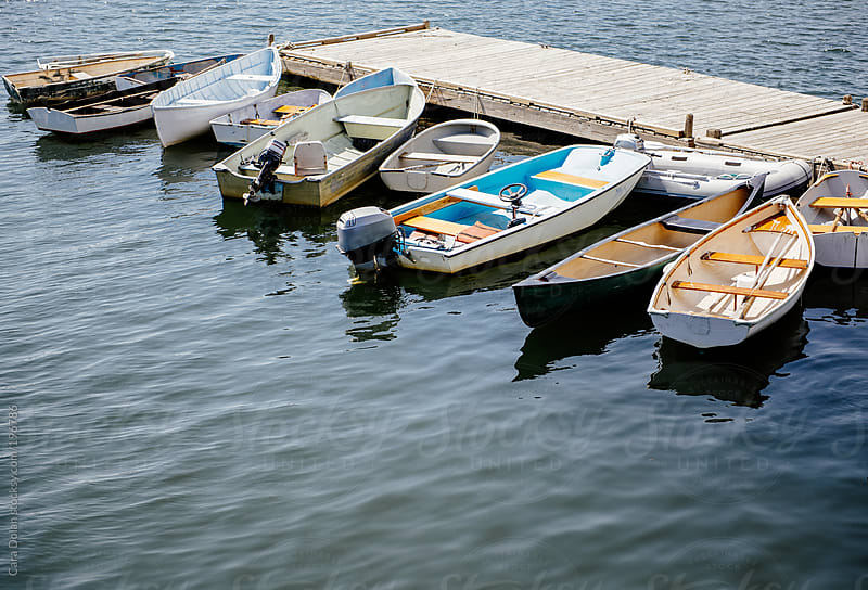 Row of small boats tied to a dock in a harbor by Cara Dolan for Stocksy United
