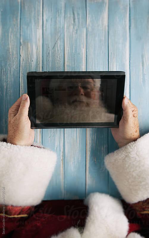 Santa Using Digital Tablet At Christmas by Sean Locke for Stocksy United
