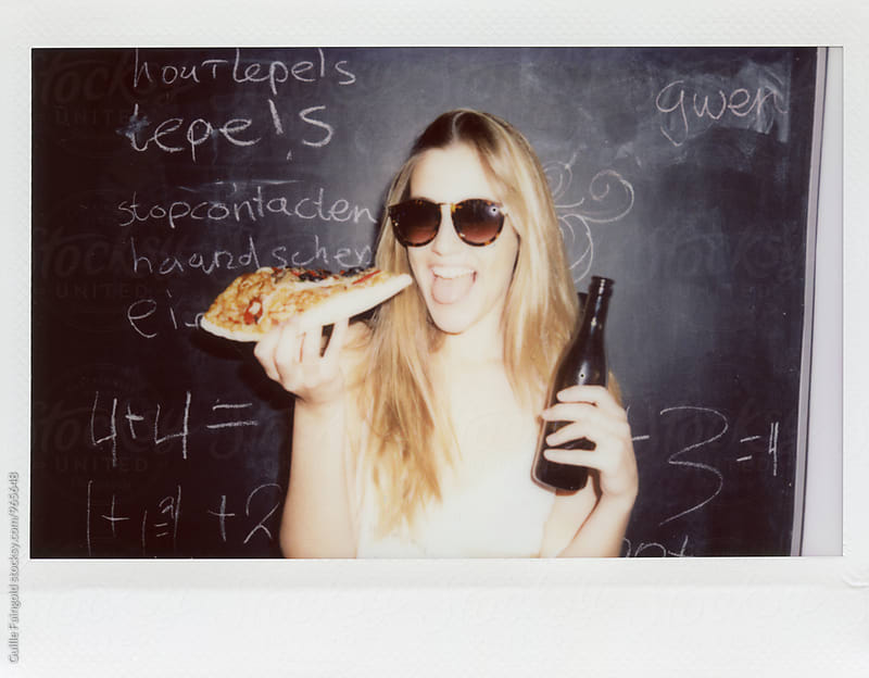 Young woman with bottle of beer and pizza showing tongue by Guille Faingold for Stocksy United