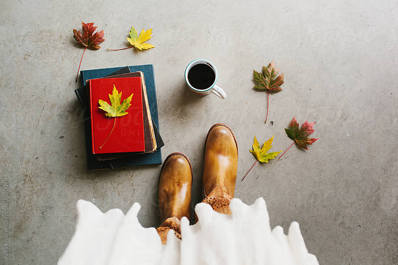 woman's boots standing amongst autumn leaves, coffee, and books by Kelly Knox for Stocksy United