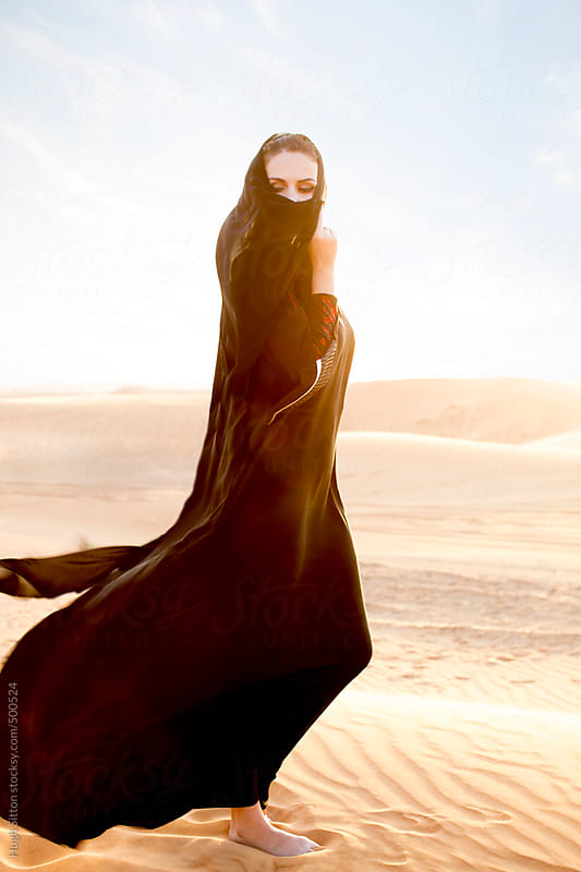 Arabian woman wearing traditional costume. Dubai desert. U.A.E. by Hugh Sitton for Stocksy United