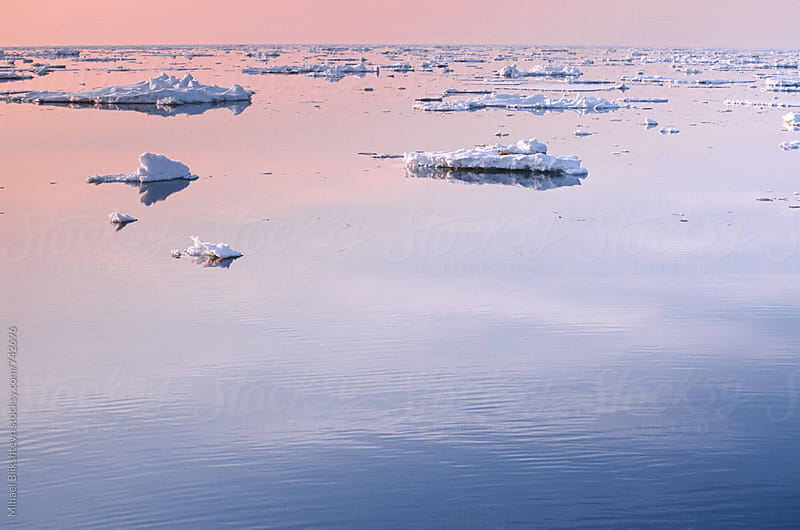 Ice floats in the middle of the sea at sunset by Mihael Blikshteyn for Stocksy United
