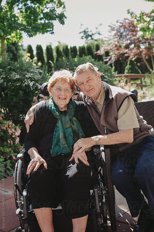 Smiling, caucasian senior couple outside with wheelchair in garden by Rob and Julia Campbell for Stocksy United