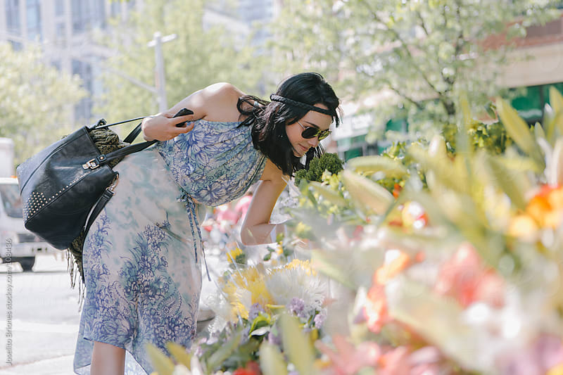 Woman in Floral Dress buying Flowers in Tribeca, New York by Joselito Briones for Stocksy United