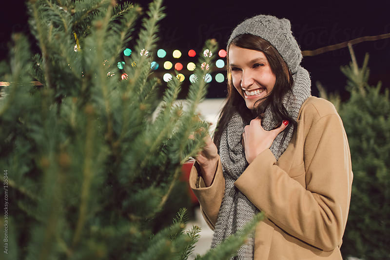 A woman picking out a christmas tree smiling by Ania Boniecka for Stocksy United