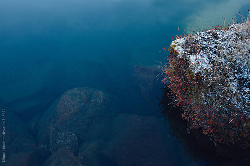 Blue water and first snow by Miquel Llonch for Stocksy United