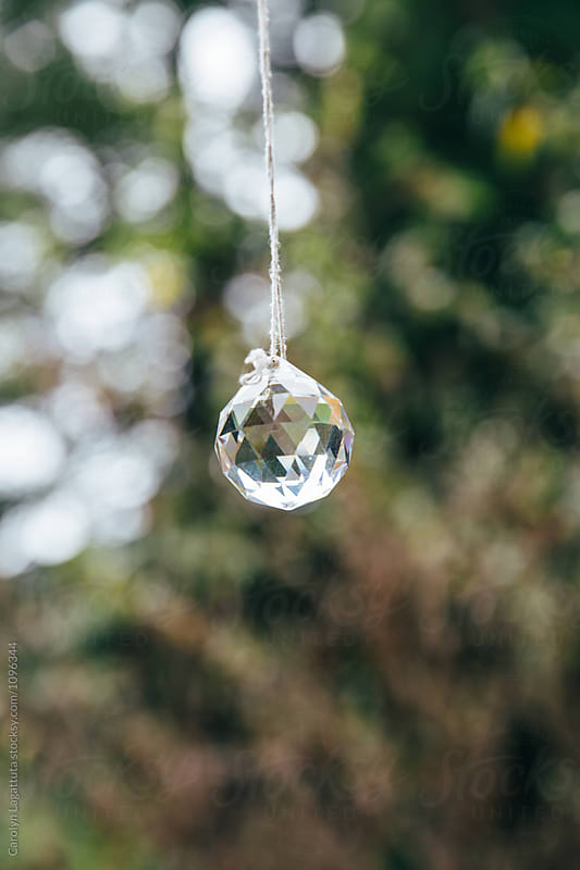 Shiny crystal hanging outside in nature by Carolyn Lagattuta for Stocksy United