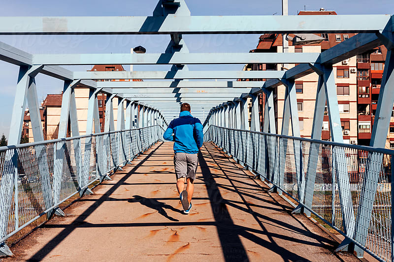 Man running over the bridge by Dimitrije Tanaskovic for Stocksy United