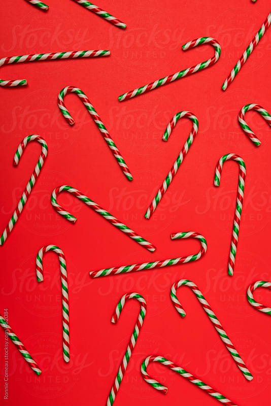 Jumble Of Candy Canes On Red Background by Ronnie Comeau for Stocksy United