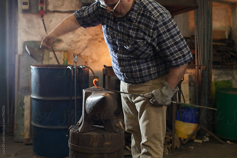 Blacksmith hammering a red-hot artifact in his workshop, Italian craftsmanship. by Luca Di Lotti for Stocksy United