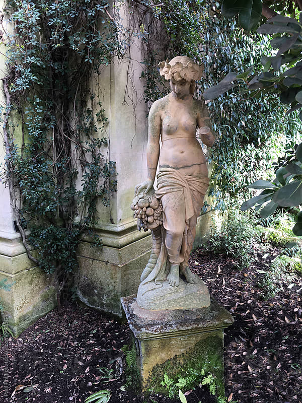 Statue of a woman in an ancient orangery with overhanging plants. by Paul Phillips for Stocksy United