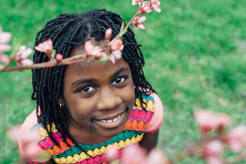 Smiling black girl by peach tree flowers by Gabriel (Gabi) Bucataru for Stocksy United